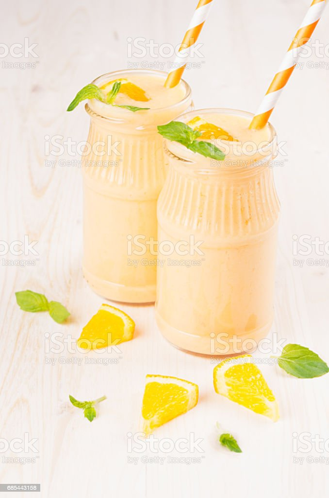 Freshly blended orange citrus smoothie in glass jars with straw, mint leaf, close up. White wooden board background. foto de stock royalty-free