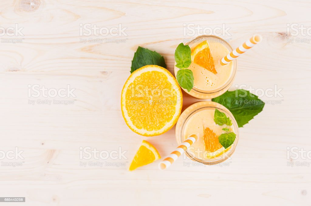 Freshly blended orange citrus smoothie in glass jars with straw, mint leaf,  cut orange, top view. White wooden board background, copy space. foto de stock royalty-free