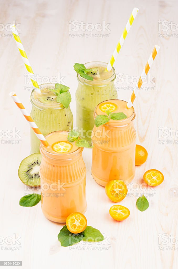 Freshly blended orange kumquat and green kiwi fruit smoothie in glass jars with straw, mint leaf, cut ripe berry, close up. White wooden board background, vertical. foto de stock royalty-free