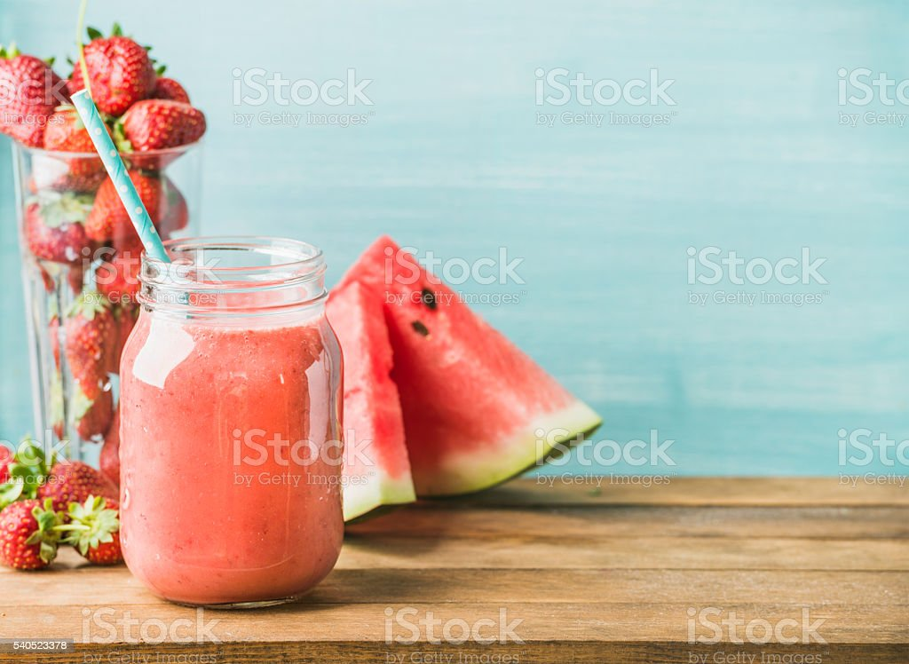 Freshly blended red fruit smoothie in glass jar with straw stock photo