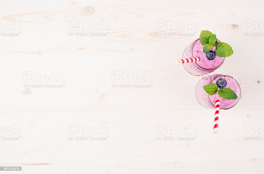 Freshly blended violet blueberry fruit smoothie in glass jars with straw, mint leafs, top view. White wooden board background, copy space.