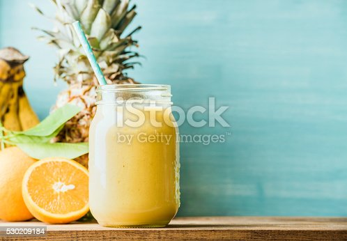 istock Freshly blended yellow and orange fruit smoothie in glass jar 530209184