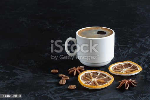 istock freshly brewed coffee with froth in a white cup with dried lemon slices, star anise and coffee beans on a black concrete textural background with copy space. angled side view. dark photo 1146128519