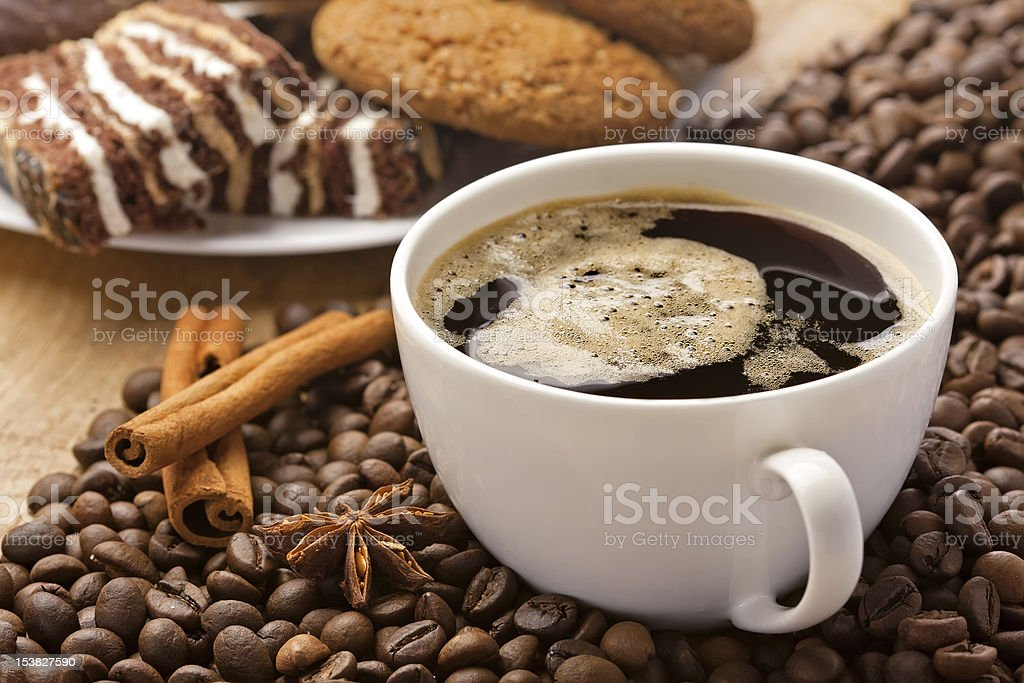 Freshly brewed cup of coffee on top of coffee beans stock photo