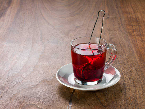 Freshly brewed herbal tea in a glass cup on wooden table