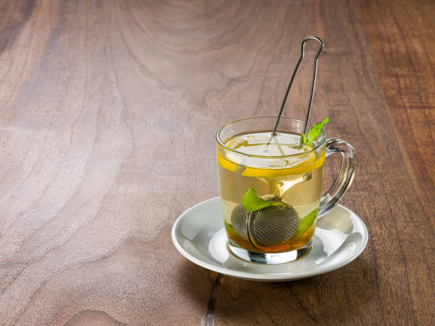 Freshly brewed tea in a glass cup on wooden table