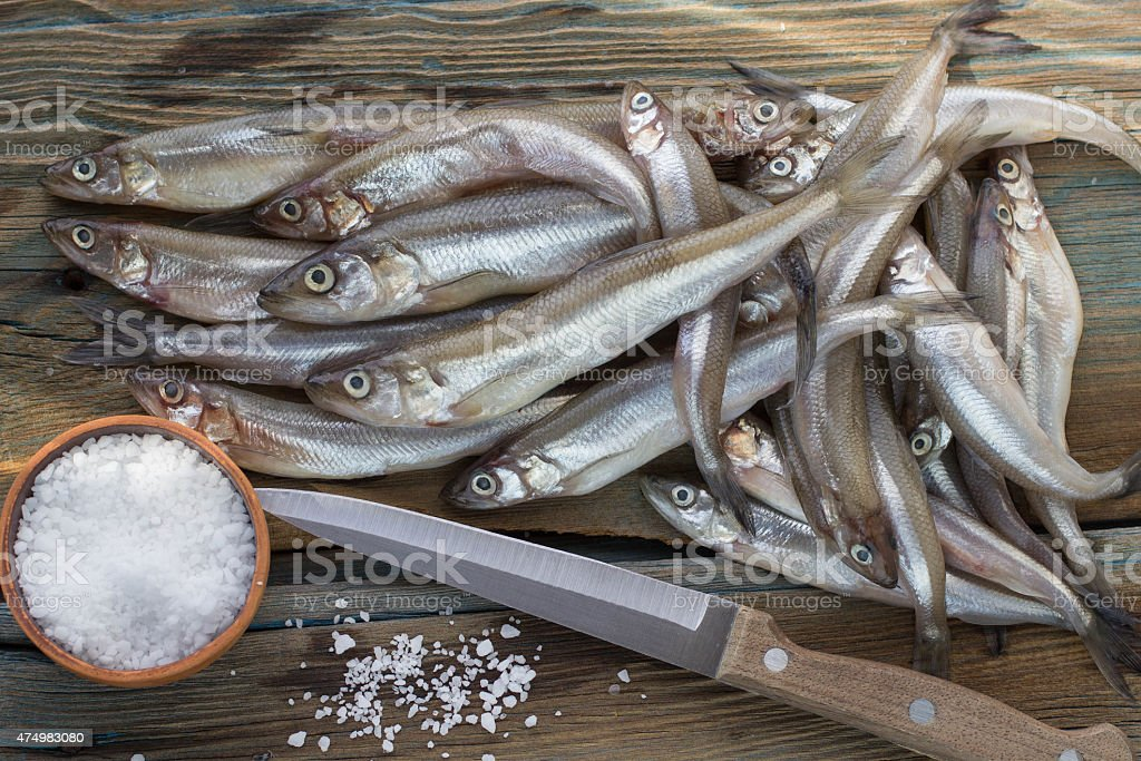 Freshly caught small fish. Smelt on a wooden surface stock photo