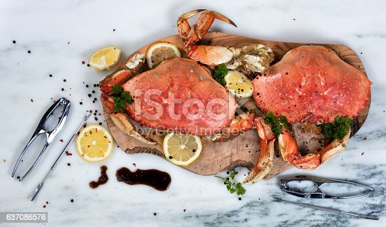 Overhead view of cooked crab on wooden server with utensils and spices
