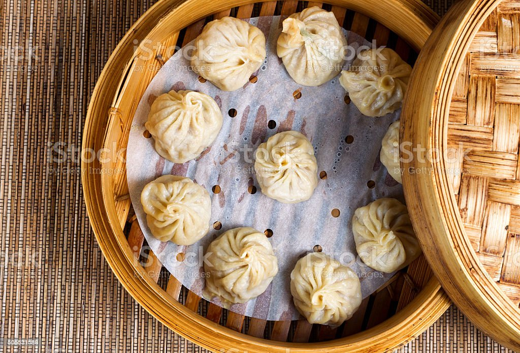 Freshly cooked dumplings inside of bamboo steamer ready to eat stock photo