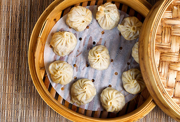 freshly cooked dumplings inside of bamboo steamer ready to eat - dumplings stock photos and pictures