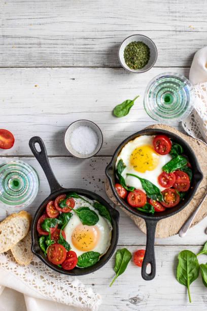 frisch gekochte eier und tomaten in einer pfanne - sonntagsbrunch stock-fotos und bilder