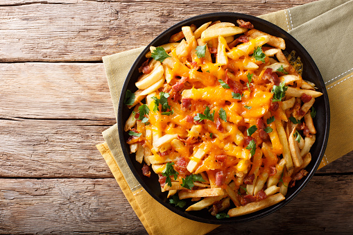 istock Freshly cooked French fries baked with cheddar cheese, bacon and parsley closeup. horizontal top view 1060410062