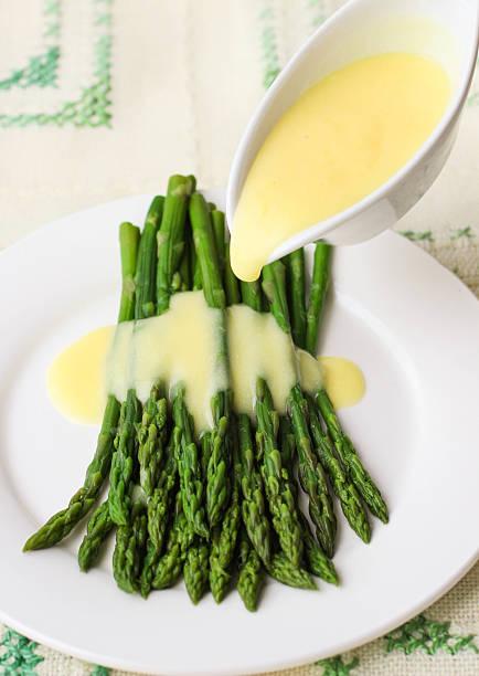 frisch zubereitete grüner spargel mit sauce hollandaise - sauce hollandaise stock-fotos und bilder
