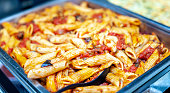 Freshly cooked Italian penne pasta in bolognese sauce in a warming tray as a catering concept.