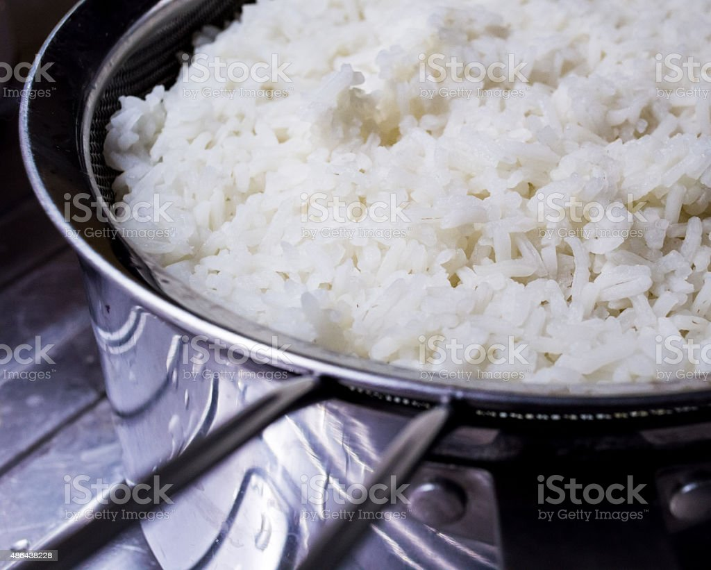 Freshly Cooked White Rice in a Strainer Near a Sink stock photo