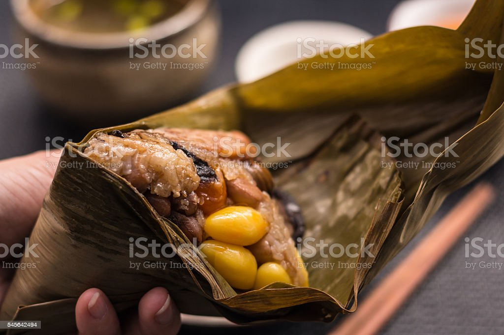 Freshly cooked Zongzi wrapped with bamboo leaf holding stock photo