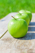 Freshly cropped geen apples on wooden table over grenn grass background.