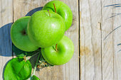 Freshly cropped geen apples on wooden table, top view