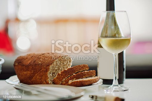 Freshly cut bread with white wine bottle and glass on a table outdoors South Africa