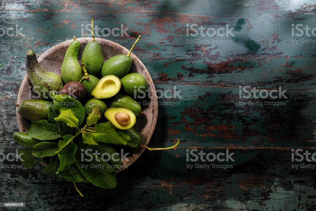 Freshly cut in half advocado halves in an old wooden bowl with other fresh ripe and unripe avocados, together with avocado leaves, on an old wooden turquoise colored table background. royalty-free stock photo