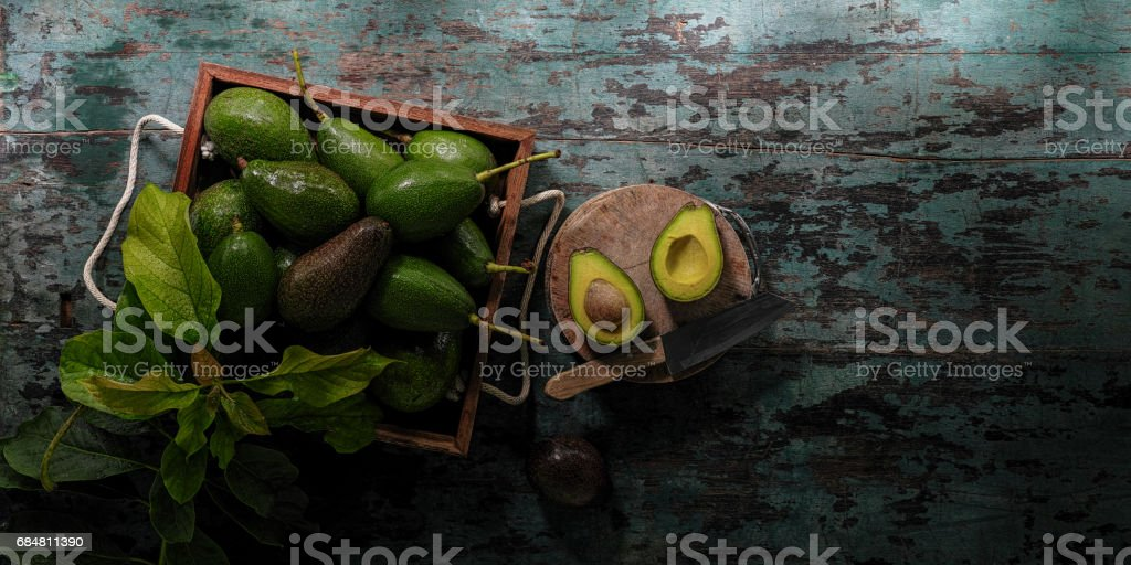 Freshly cut in half advocado on a cutting board with a knife, on an old turquoise coloured table next to a wooden crate with fresh ripe and unripe advocados and some advocado leaves. stock photo
