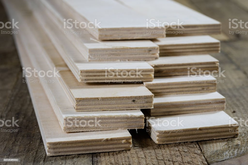 Freshly cut plywood. Plywood strips arranged in stacks. Warehouse with plywood. Materials for carpentry. Old warehouse. stock photo