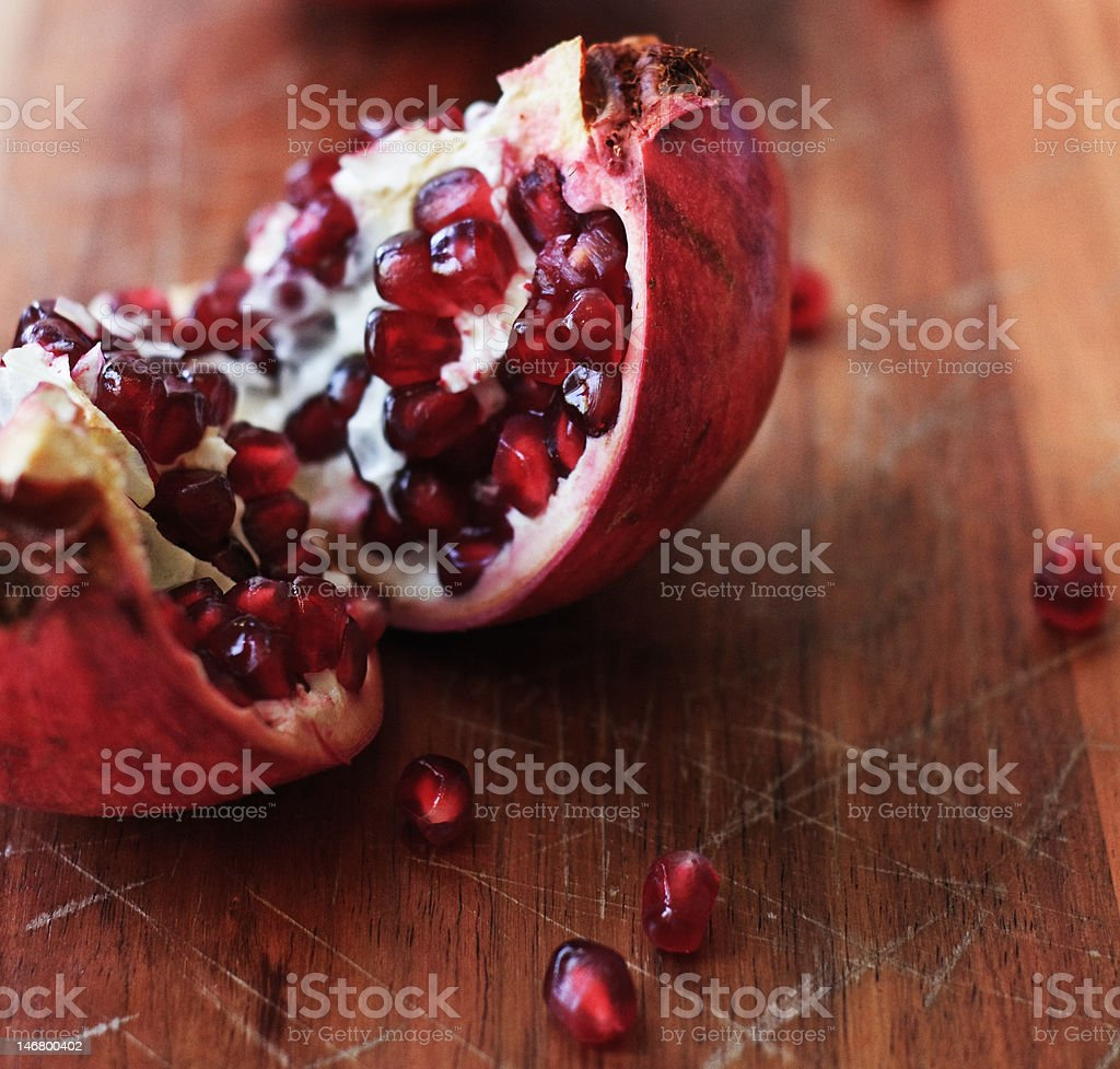 Freshly cut pomegranate with seeds on wood royalty-free stock photo