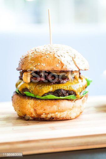 Close up image of a freshly flame grilled beef burger loaded with melted cheese and crispy bacon with fresh green salad leaves, sandwiched between a toasted sesame seed bun. White backgroung with room for copy space.