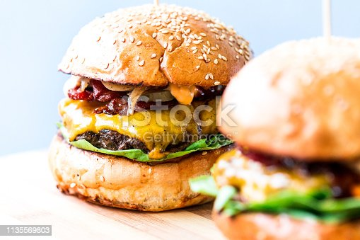 Close up image of two freshly flame grilled beef burgers loaded with melted cheese and crispy bacon with fresh green salad leaves, sandwiched between a toasted sesame seed bun. White backgroung with room for copy space.