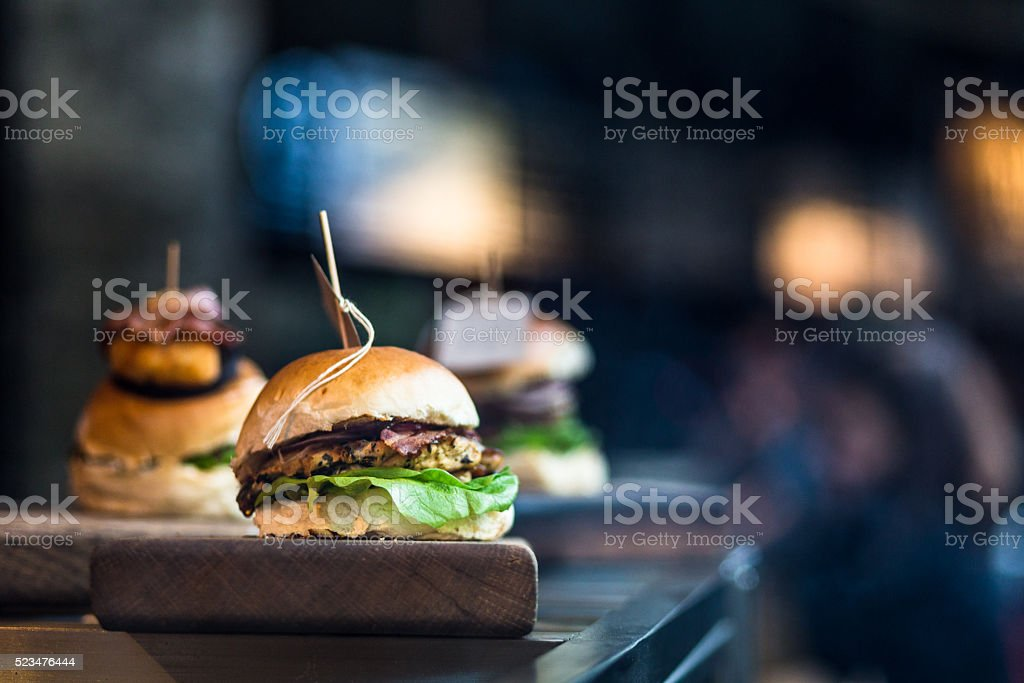 Freshly Flame Grilled Burgers at Food Market Close up image of a freshly flame grilled burger inside a bun, wilth lettuce, red onion, melted cheese and tomato. There are a few more burgers defocused in the background. The burger rests on a wooden board and the background is pleasantly defocused, leaving plenty of room for copy space. Horizontal colour image processed from an original RAW file,  American Culture Stock Photo