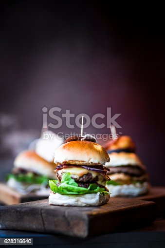 istock Freshly flame grilled burgers in a row on wooden board 628316640