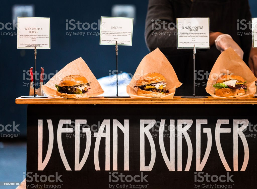 Freshly flame grilled Vegan burgers displayed in a row Close up image of a selection of freshly flame grilled vegan burgers in a row on a wooden counter. Each of the burgers has its own label, on which is written the contents of the burger. The burgers are sandwiched between glazed buns, and presented on beds of fresh green lettuce and stuffed with melted cheese and red onion. Horizontal colour image with copy space. American Culture Stock Photo