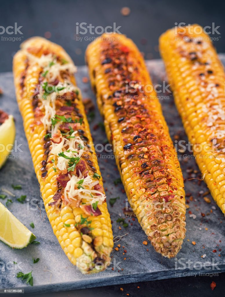 Freshly Grilled Corn on The Cobs With Various Toppings stock photo