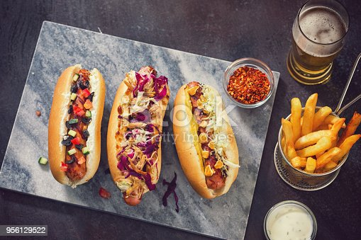 High angle view of freshly grilled  hot dogs with various condiments like barbecue sauce,pulled pork,coleslaw,sauerkraut,pretzels,tzatziki,cucumber and kalamata olives