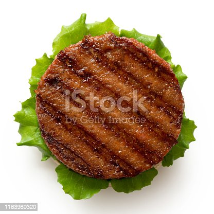 Freshly grilled plant based burger patty on bun with lettuce isolated on white. Top view.