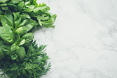 Freshly harvested herbs, bunches of fresh herb on white marble background from above. Bundles of organic basil, dill and arugula from local farmers. Top view. Flat lay. Copy space.