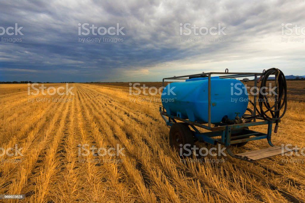 Freshly harvested wheat field and farming irrigation equipment under a cloudy sky. stock photo