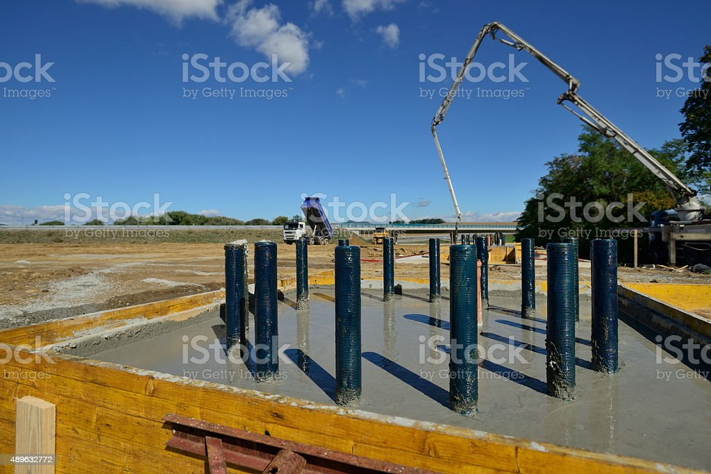 Freshly laid concrete bottom plate with massive screws well-oiled stock photo