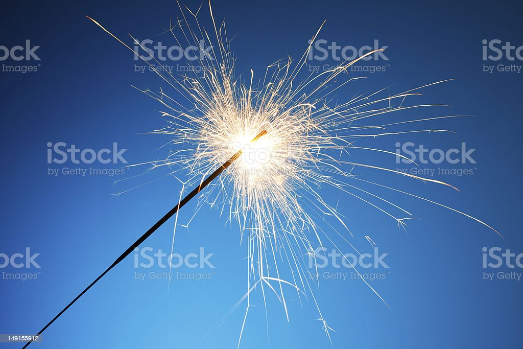 Freshly lit sparkler on blue background stock photo