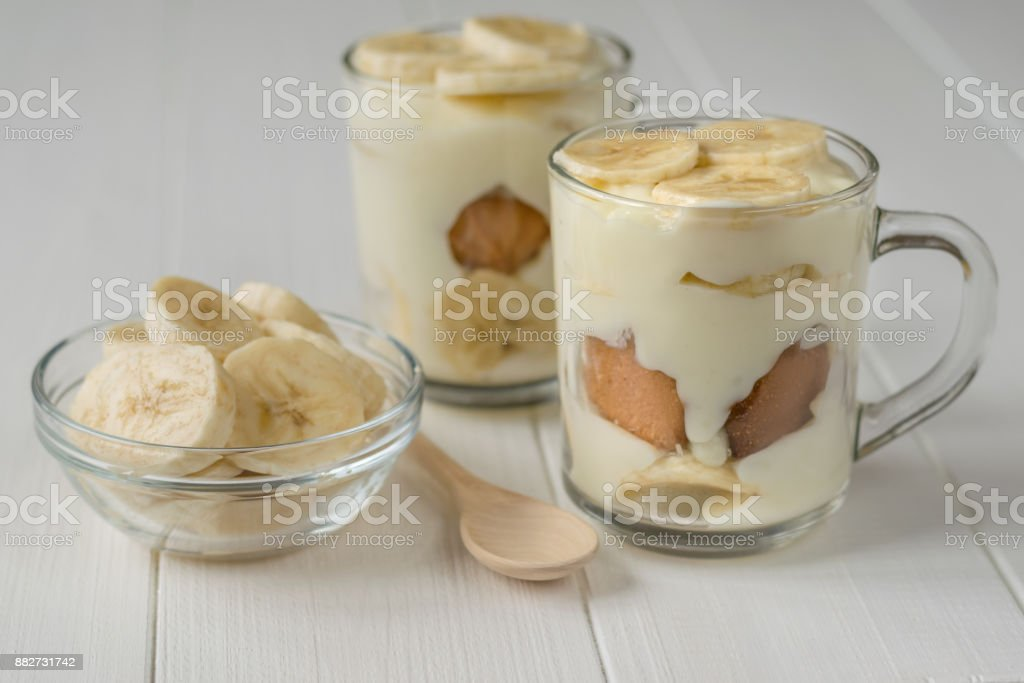 Freshly made banana pudding in the circles and the slices of banana on a white table. stock photo