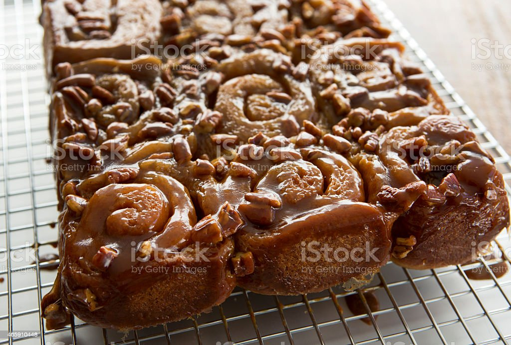 Freshly Made Caramel Pecan Rolls on a Cooling Rack. stock photo