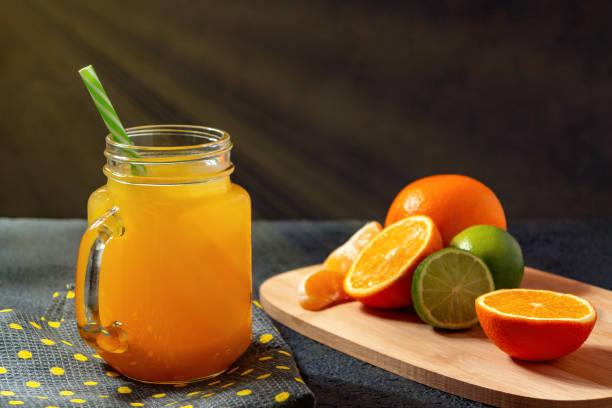 Frisch zubereiteter Zitrussaft aus Orangen, Grapefruit und Limette in einem Glasbecher mit Stroh auf schwarzem Tisch – Foto
