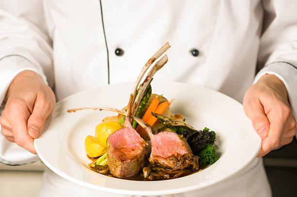 A freshly made rack of lamb being held by a chef  Chef holding a rack of lamb entree main course stock pictures, royalty-free photos & images