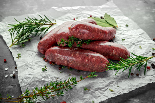 freshly made raw breed butchers sausages in skins with herbs on crumpled paper - sausage stock photos and pictures