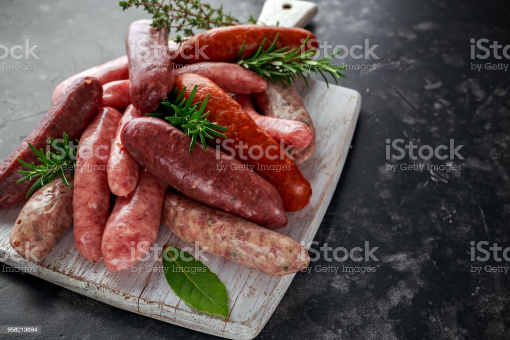 Freshly made raw breed butchers sausages mix in skins with herbs on white cutting board stock photo