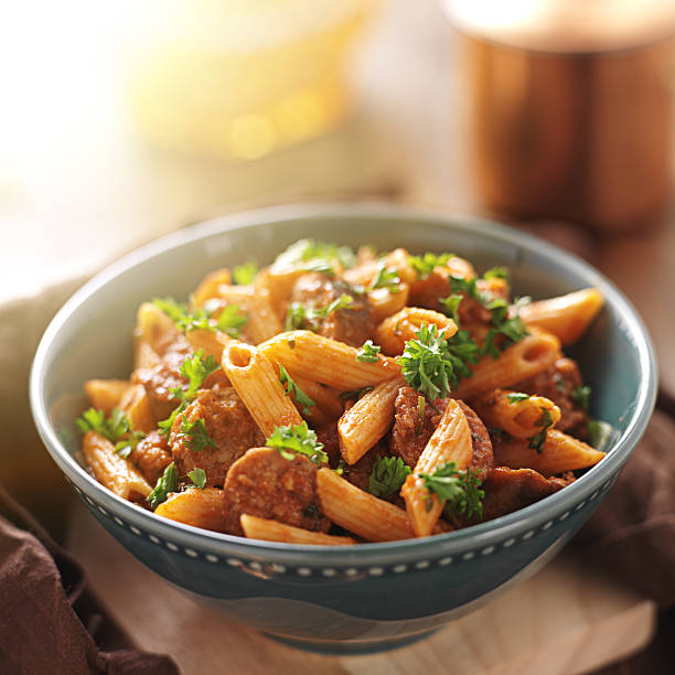 Freshly made rigatoni pasta with sausage and garnishing  close up photo of a bowl of rigatoni pasta with sausage shot with extreme selective focus. rigatoni stock pictures, royalty-free photos & images