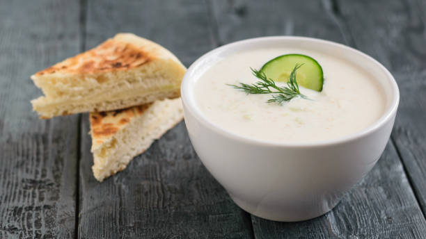 Freshly made tzatziki in a white bowl with bread on a dark wooden table. stock photo