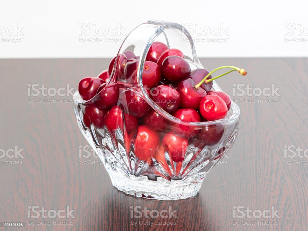 Freshly picked cherries in a crystal basket stock photo