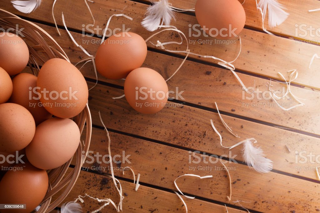 Freshly picked eggs in basket on wood table top view stock photo