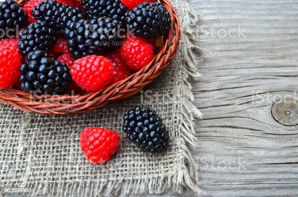 Foto de Frescas Colhidas Orgânicos Amoraspretas E Framboesas Em Uma Cesta Na Mesa De Madeira Velha Saudável Comer Vegan Alimentar Ou Dieta Conceito e mais fotos de stock de Agricultura
